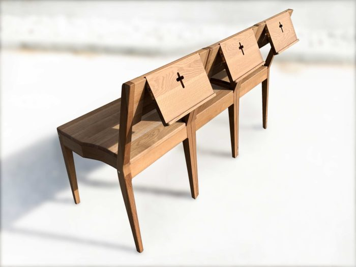 Three church chairs in pew with Bible holders made of oak wood.